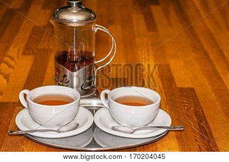 Two cups of tea and teapot on a wooden table