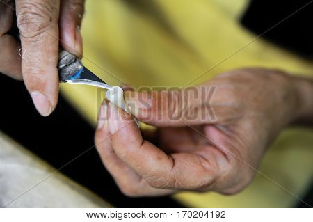 Closeup of worker's hands carving a plastic detail