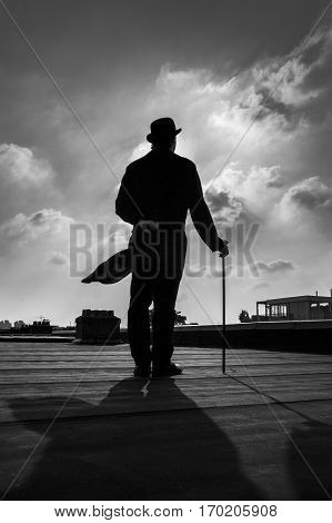 Black and white silhouette of a an elegant gentleman wearing a long a coattail with a cane and a bowler hat