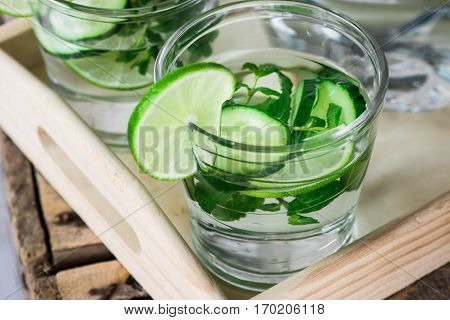 Glasses with detox infused cucumber water with lime and mint on wooden tray, pitcher,close up