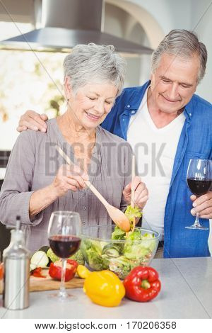Senior woman preparing salad while man standing at counter in kitchen