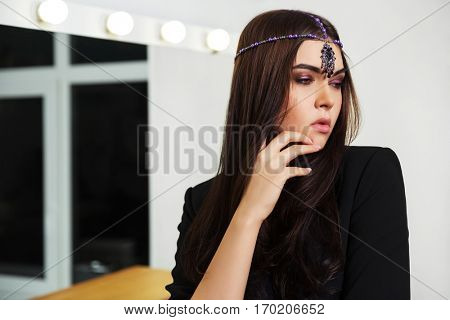 Sad young woman in black jacket next to makeup mirror Stylish fashion model indoors