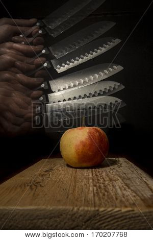 red and yellow apple on a rustic wooden plank and black background with a hand holding a knife going down in slow motion to the apple