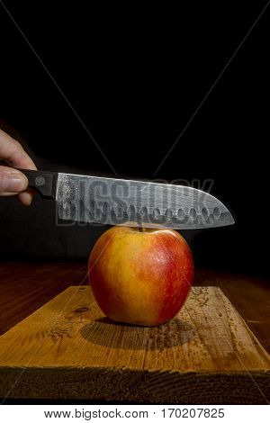 sharp knife about to cut a red and yellow apple on a rustic wooden plank with black background