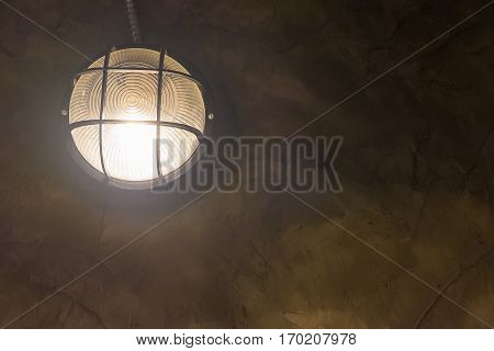 Tungsten Wall Lamp Glowing Over Dark Background.
