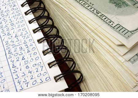 Ledger and one hundred dollar banknotes. Financial accounting concept.