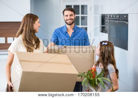Happy family holding box while relocating house
