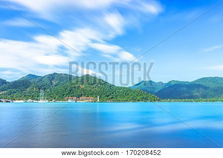 scenic view of the harbour with mountain background against cloudy sky at Bang-Bao Koh Chang Island (Thailand).