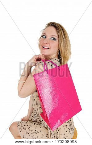 A beautiful young woman sitting in a dress on a chair with a shopping bag over her shoulder isolated for white background.