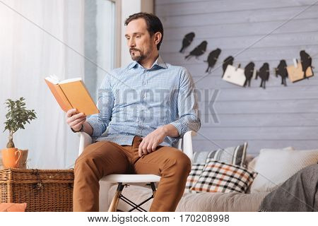 Interesting story. Handsome pleasant brunette man holding a book and reading a story while sitting on the chair