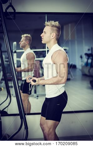 Handsome blond young man exercising triceps on gym equipment, shot from a side