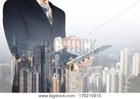 Double Exposure Of Businessman Using Tablet On Building Background..