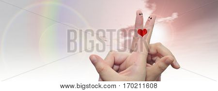 Concept or conceptual human or female hands with two fingers painted with a red heart and smiley faces over rainbow sky background banner for valentine, romantic, love, couple, young, family wedding