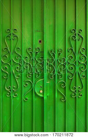 Detail of green metallic door with curly decorative elements
