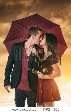 Girlfriend and boyfriend having a passionate kiss framed in one umbrella