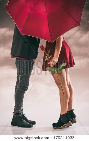 Girlfriend and boyfriend having a passionate kiss hidden behind the umbrella