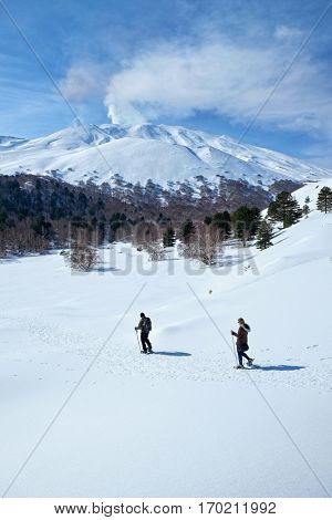 two hiker snowshoeing in winter Etna Park, Sicily