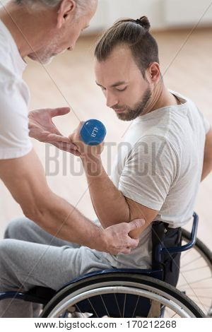 Concentrated on the successful result. Handsome muscular young disabled man holding the dumbbell and having the lesson with the orthopedist in the gym while doing gymnastics