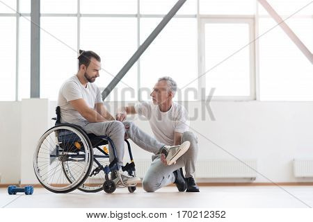Working with disabled people. Masterful involved aged physical therapist helping the disabled man and providing a rehabilitation session while expressing concentration
