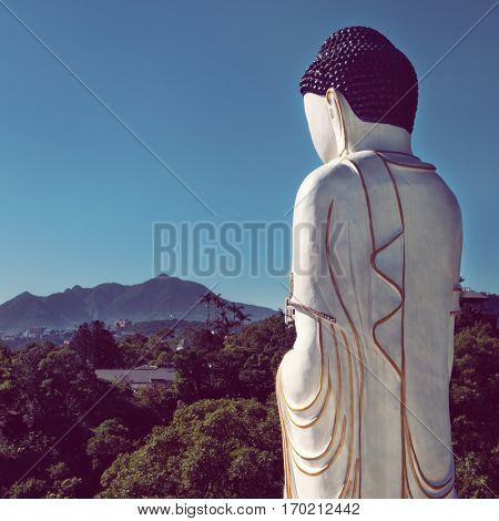 Taipei - December 2016: White Buddha statue with lush landscape in background. Thermal Valley, Beitou Hot Spring