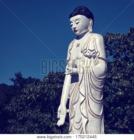 Taipei - December 2016: White Buddha statue with trees in background. Thermal Valley, Beitou Hot Spring