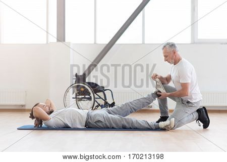 Doing my job properly. Confident skilled aged physical therapist helping the disabled man and providing a rehabilitation while expressing positivity and holding the leg of the patient