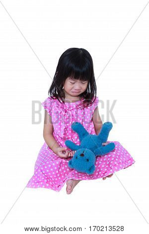 Child with tears. Asian girl sitting with toy bear sadden and crying. Isolated on white background. Negative human emotion facial expression feeling reaction. Studio shot.