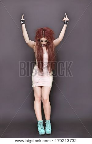 Funky young woman making rebellious gestures over black background