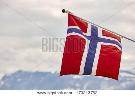 Norwegian flag over a mountain cloudy winter landscape. Horizontal
