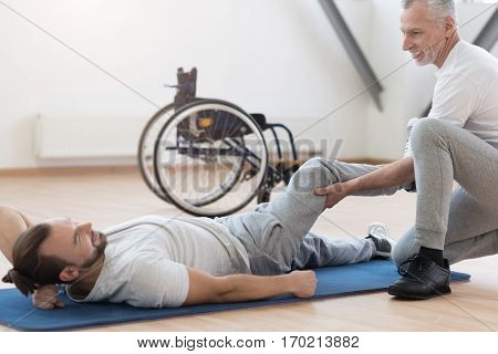 Friendly atmosphere in the gym. Muscular skilled aged physical therapist stretching the handicapped and providing a rehabilitation session while holding the leg of the patient
