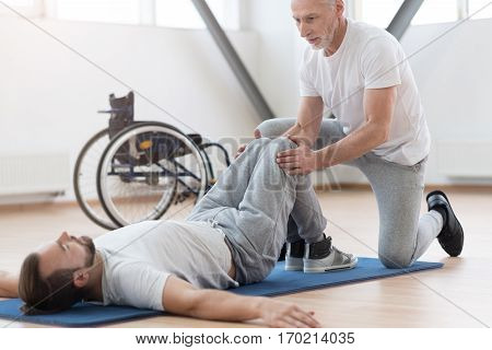Friendly atmosphere during our training. Experienced skilled aged physical therapist stretching the handicapped and providing a rehabilitation session while holding legs of the patient