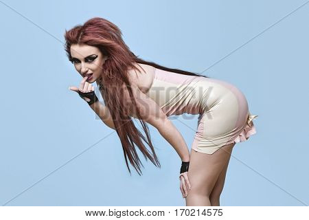 Portrait of seductive young funky woman bending over blue background