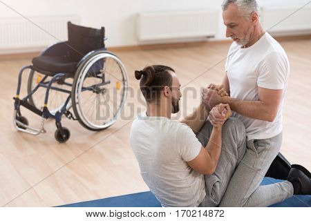 Developing strength. Openhearted athletic powerful orthopedist stretching the handicapped and assisting him while holding arms of the patient
