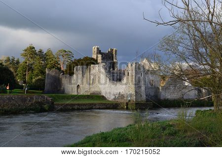 Desmond castle ruins with dark storm clouds swirling above it.