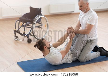 Doing sit ups. Powerful athletic muscular orthopedist stretching the disabled and assisting him while holding arms of the patient and expressing concentration