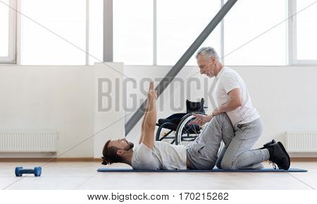 Proud of my disabled patient. Cheerful athletic aged physical therapist stretching the disabled and assisting while holding legs of the patient and counting