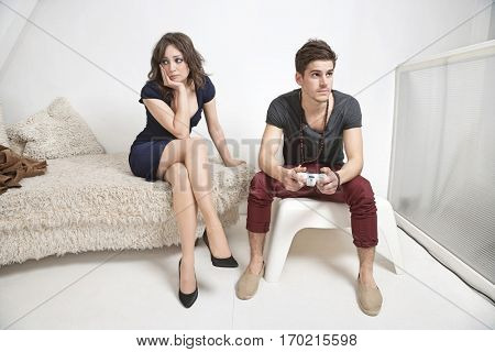 Young bored woman sitting on sofa with man playing video game