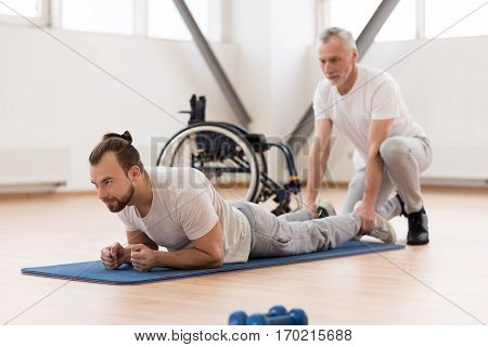Full of concentration. Skillful helpful bearded physical therapist stretching the disabled man and assisting while holding legs of the patient and expressing positivity