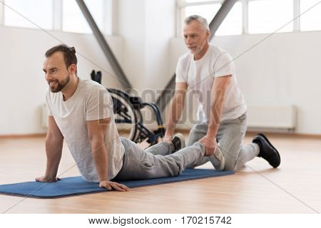 Full of positive emotions. Athletic helpful bearded orthopedist stretching the disabled man and assisting while holding legs of the patient and expressing positivity