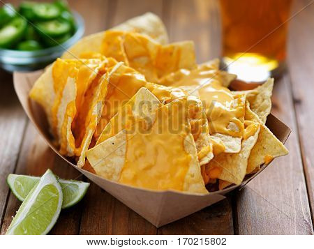 nachos and cheese with lime shot with selective focus