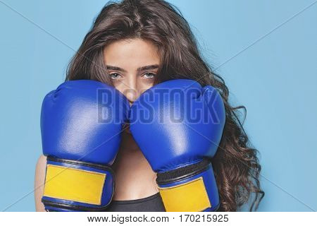 Portrait of a young female boxer with fists up against blue background