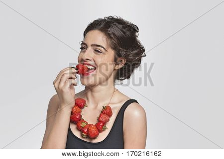 Happy young woman wearing strawberry necklace as she eats one piece over gray background
