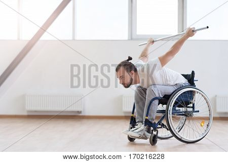Sport as important part of my life. Muscular confident purposeful invalid sitting in the wheelchair in the gym while exercising and holding the metal barbell