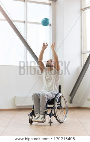 Enjoying throwing up the ball. Cheerful joyful young handicapped sitting in the wheelchair in the gym and smiling while exercising and playing with the ball