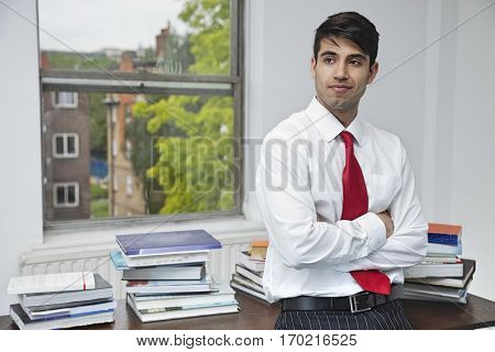 Portrait of a confident businessman with arms crossed looking away in office