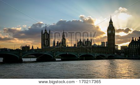 Dramatic backlit skies to the key London landmark The Palace of Westminster the seat of British government with Big Ben and Westminster Bridge in the foreground.