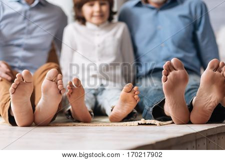 Three generations. Positive happy delighted family sitting together and showing their feet while being in a great mood