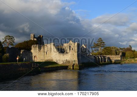 Sun shining on the ruins of Desmond Castle and Maigue River.