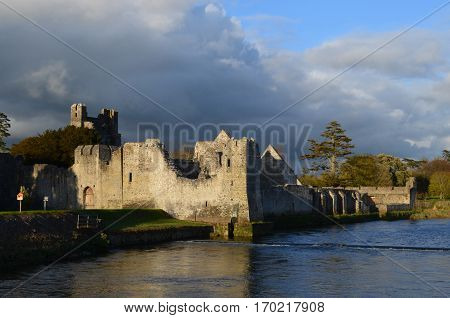 Sun shining through the storm clouds on Desmond Castle in Ireland.
