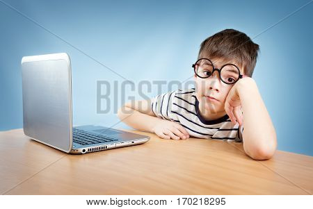 seven years old child in glasses sitting with a laptop at table